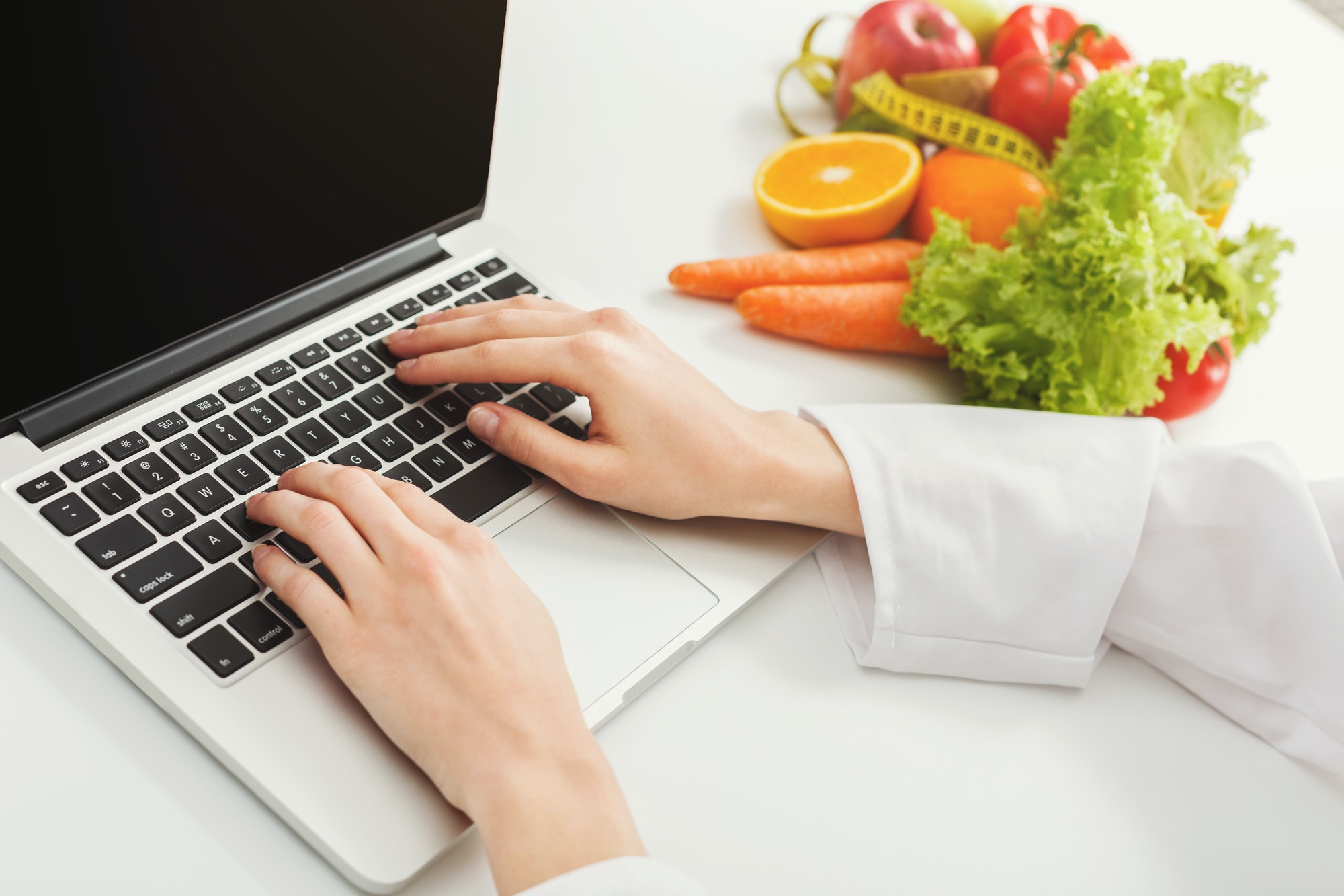 Female nutritionist working on laptop