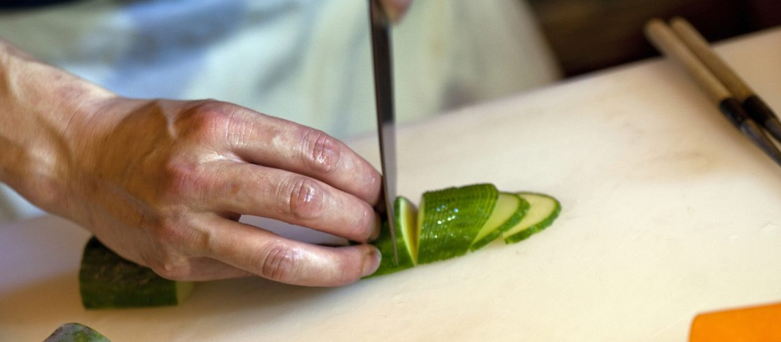Chef cutting vegetable in the kitchen of a restaurant