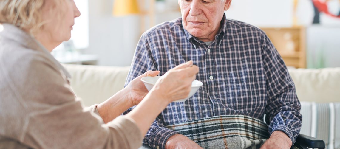 Senior grey-haired man in wheelchair looking at spoon with soup while his carer or wife feeding him by dinner